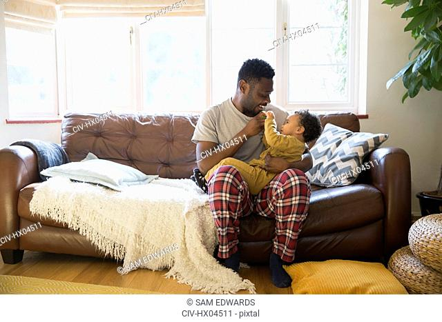 Affectionate father in pajamas cuddling with baby son on living room sofa