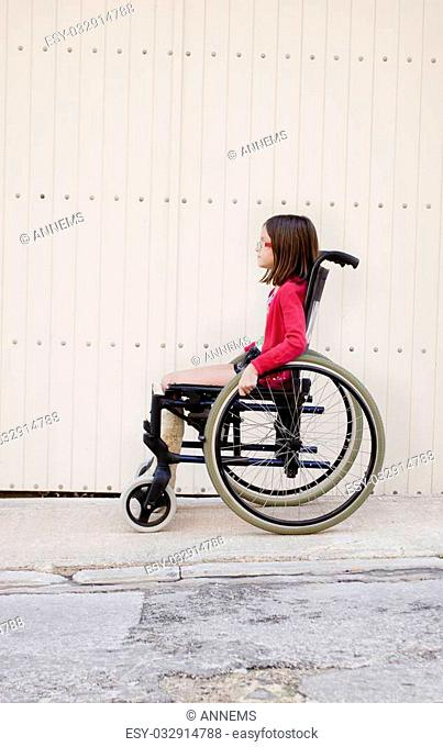 A young girl sitting outside on the sidewalk or pavement in a wheelchair with a broken leg in a cast