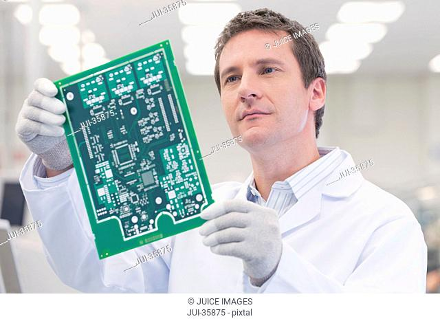 Engineer examining printed circuit board in manufacturing plant