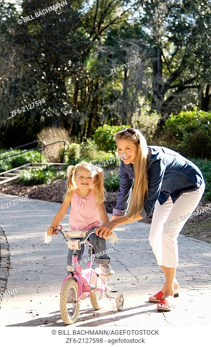 beautiful young mother and daughter riding bike and having fun outside in a park