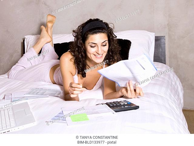 Persian woman paying bills on bed