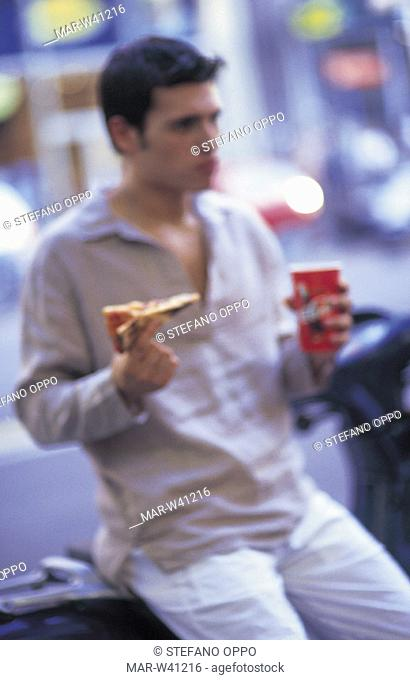 young man eating pizza on scooter