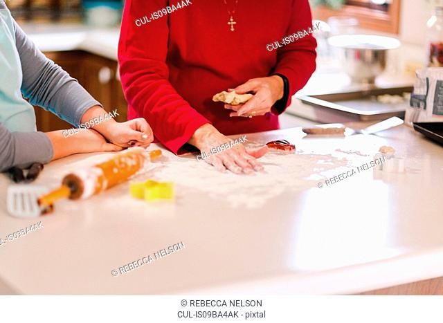 Girl and grandmother preparing flour on kitchen bench, mid section