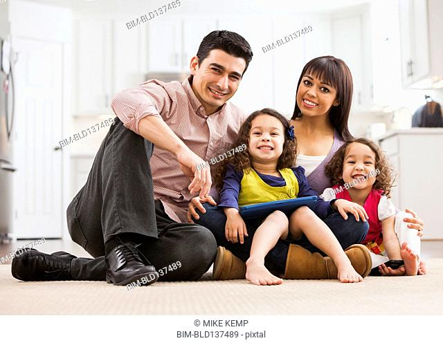 Family using tablet computer on living room floor