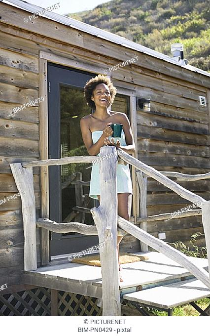 African American woman on porch of cabin with coffee