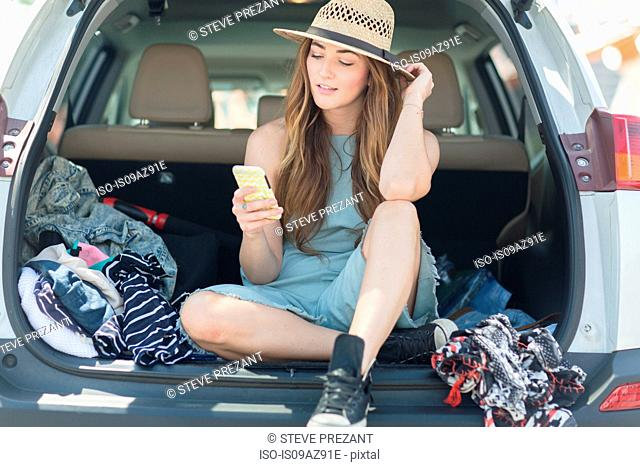 Woman in car boot looking at smartphone