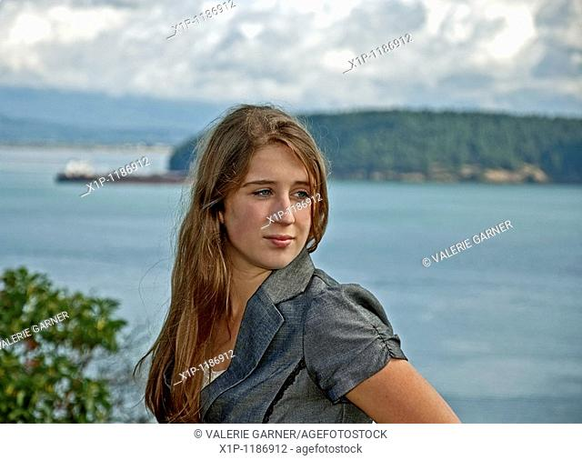 This pretty green eyed Caucasian, seventeen year old girl is overlooking an ocean scenic with stormy skies and a barge ship out in the distance  She's got long...