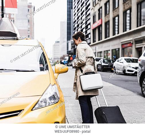 USA, New York City, woman in Manhattan at taxi