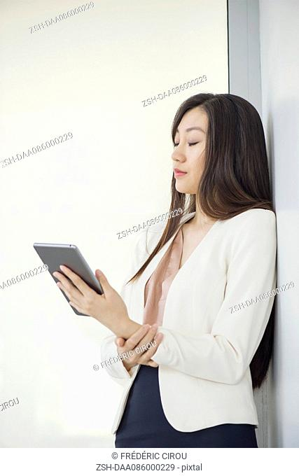 Businesswoman leaning against wall with eyes closed, holding digital tablet
