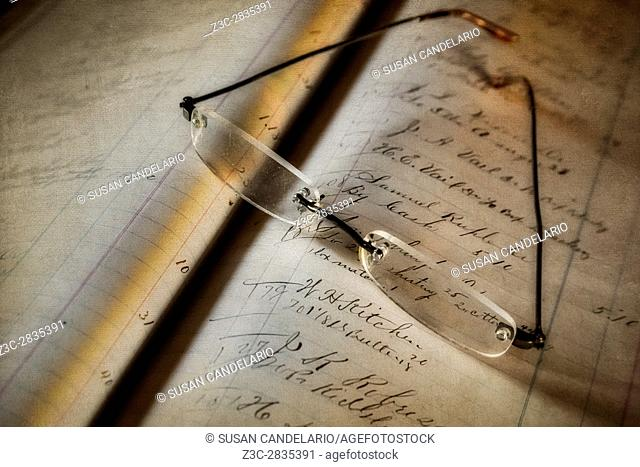 Accounting And Bookkeeping - Vintage bookkeeping ledger with eyeglasses resting on top