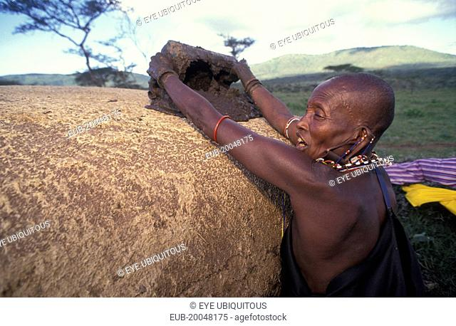 A Maasai woman covers her hut with cow dung which has the effect of waterproofing the roof