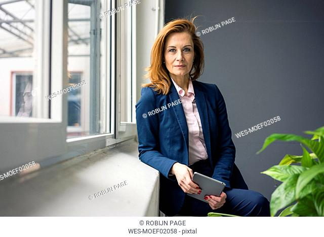 Successful businesswoman standing at window, holding digital tablet