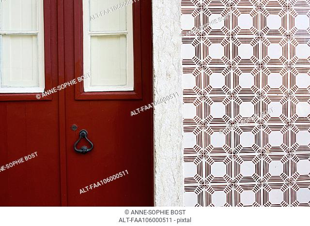 Red door and ornate tiled wall