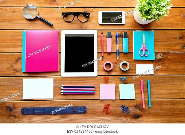 education, school supplies, art, creativity and object concept - close up of stationery and tablet pc computer with smartphone on wooden table