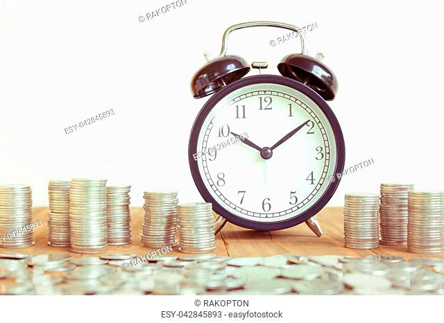 Stack of coins with black fashioned alarm clock for display planning money financial and business accounting concept, time is money concept with clock and coins
