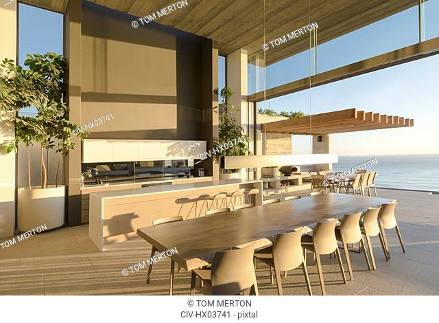 Sunny modern, luxury home showcase interior dining table with ocean view