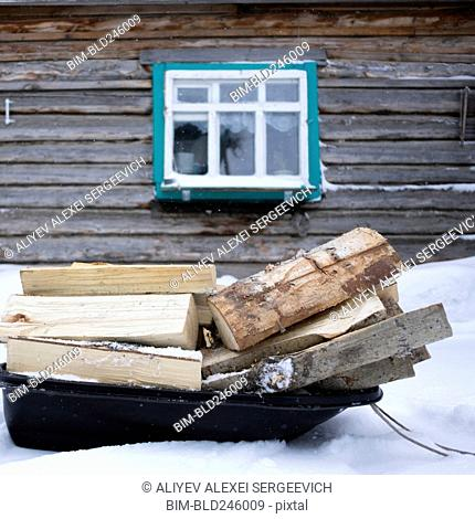Firewood on sled in snow outside cabin