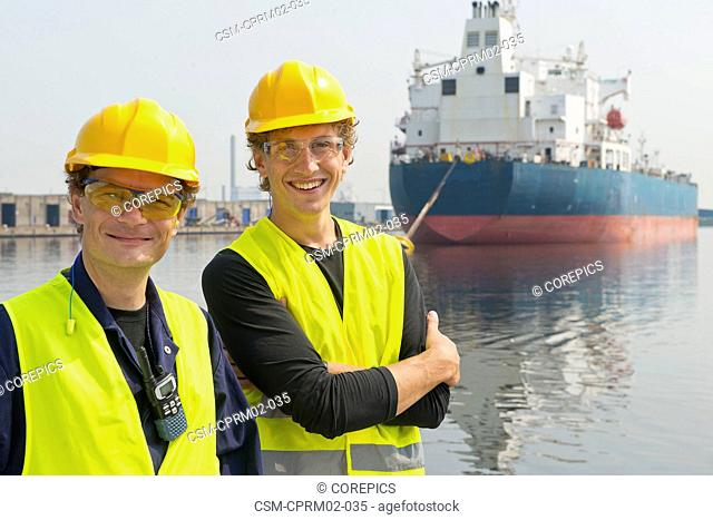 Happy, smiling dockers posing in front of a large industrial oil tanker