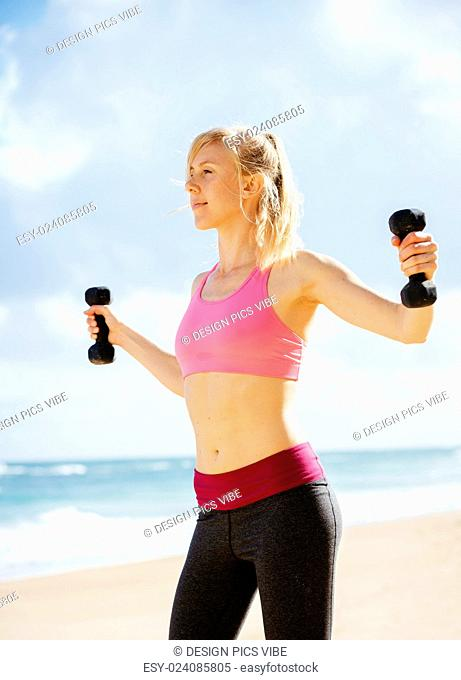 Fitness woman with barbells working out. Exercising outdoors at the beach