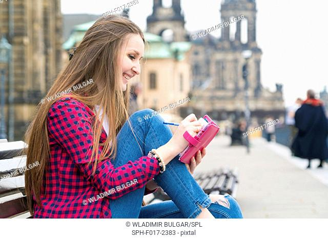 MODEL RELEASED. Young woman making notes in notebook, Dresden, Germany