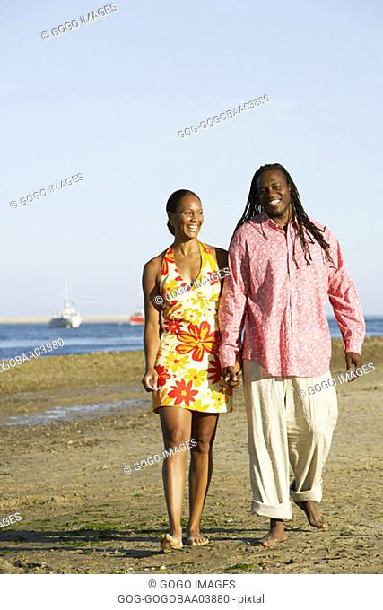 Young African couple walking on the beach hand-in-hand
