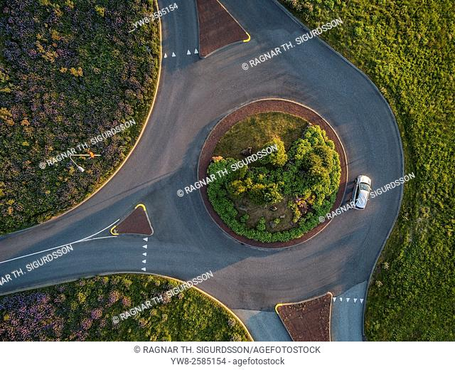 Aerial view-single car in a traffic circle, summertime, Reykjavik, Iceland. Image shot with a drone
