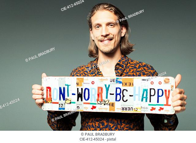 Portrait smiling young man holding Dont Worry Be Happy license plates