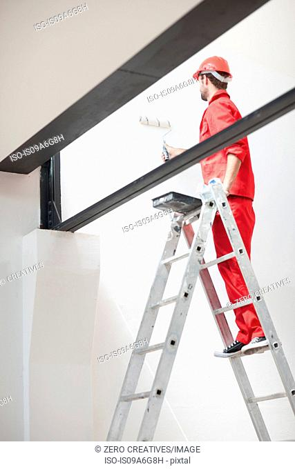Decorator on ladder painting interior wall