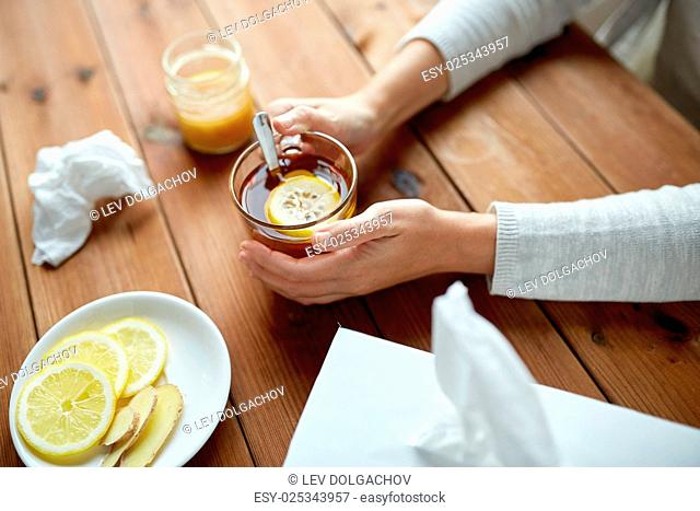 health, traditional medicine and ethnoscience concept - ill woman drinking tea with lemon, honey and ginger and paper wipes box on wooden table