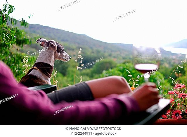 Young woman drinks a cup of wine at sunset in a terrace with views to the valley