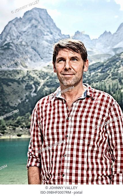 Smiling man standing by lake