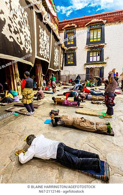 Tibetan pilgrims prostrating themselves in Barkhor Square, outside the Jokhang Temple (the most sacred temple in Tibet), Lhasa, Tibet, China
