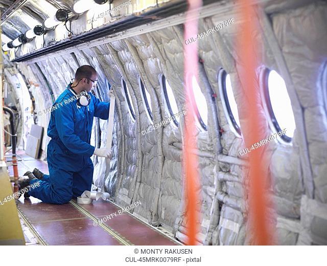 Worker measuring airplane window