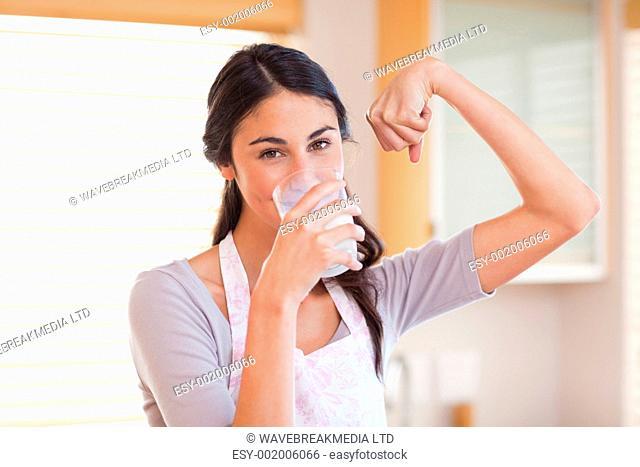 Healthy woman drinking milk in her kitchen