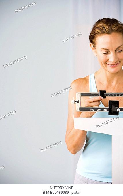Mixed race woman checking weight on scale
