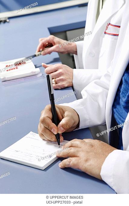 Close up of pharmacist writing on prescription pad