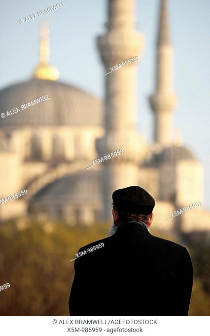 Turkish man in Sultanahmet looking at the Blue Mosque at sunset