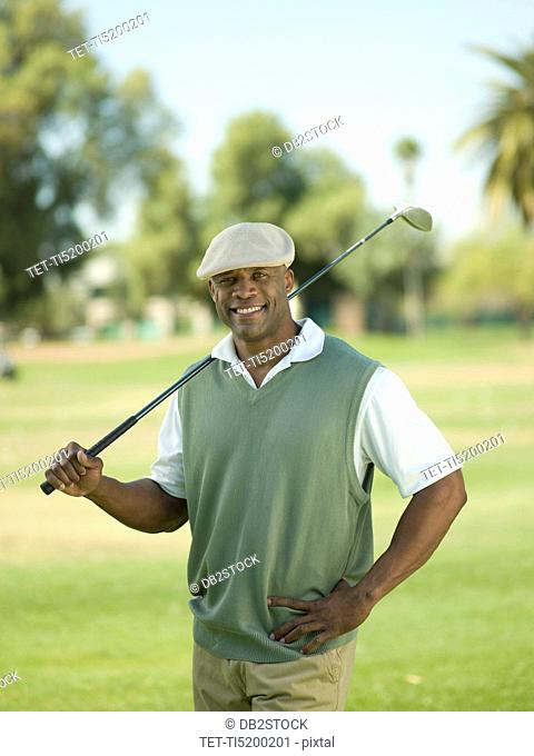 Smiling man on golf course holding golf club