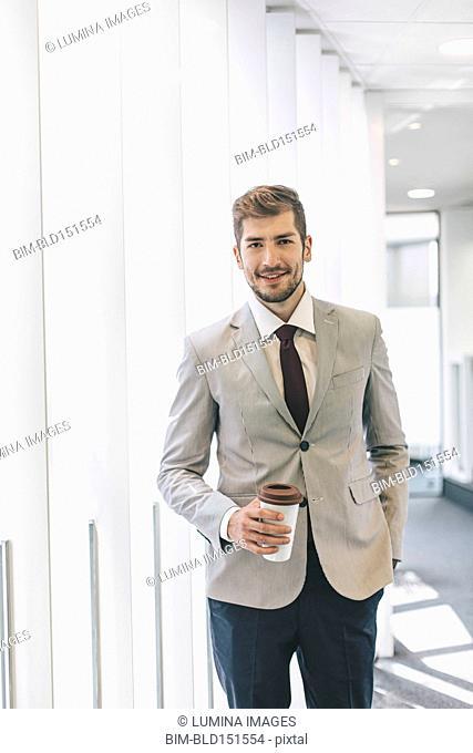 Caucasian businessman drinking coffee in office corridor