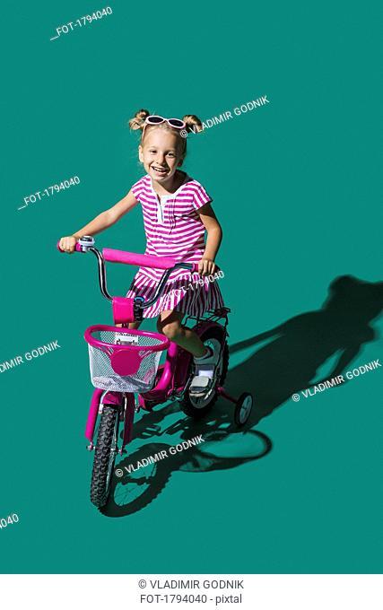 Portrait smiling girl bike riding against green background