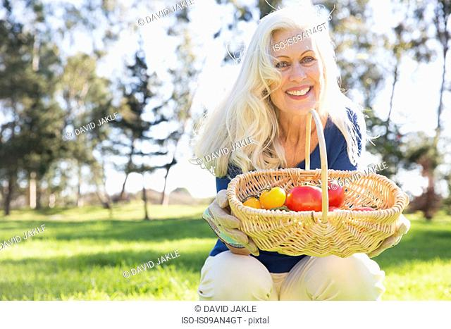 Senior woman carrying basket of tomatoes, Hahn Park, Los Angeles, California, USA