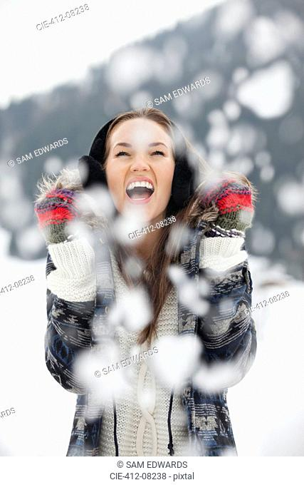 Enthusiastic woman enjoying falling snow