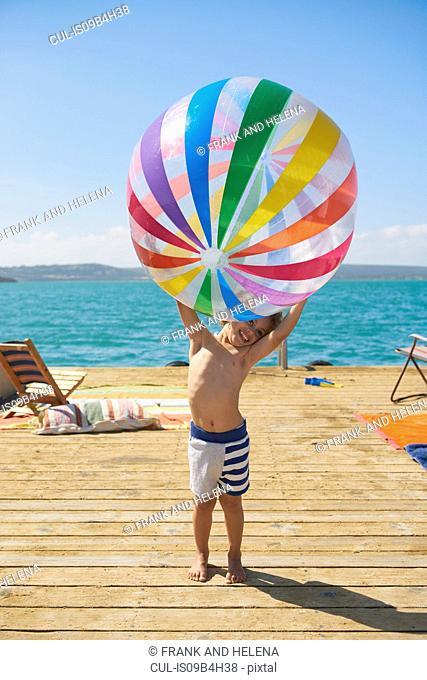 Boy holding beach ball on houseboat sun deck, Kraalbaai, South Africa