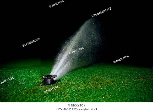 automatic lawn sprinkler spraying water over golf course green grass at night