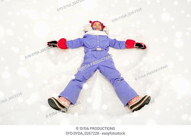 happy little girl making snow angels in winter