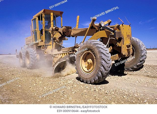 large earth mover grading an outback road