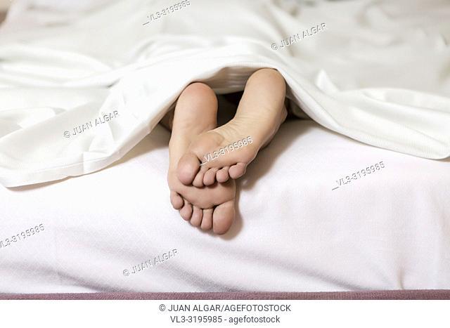 Crop shot of female soft feet lying on white bed under blanket