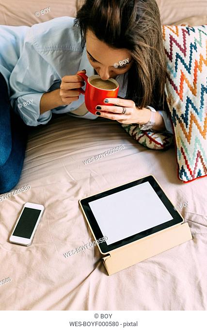 Young woman sitting on bed, coffee cup, digital tablet and smartphone