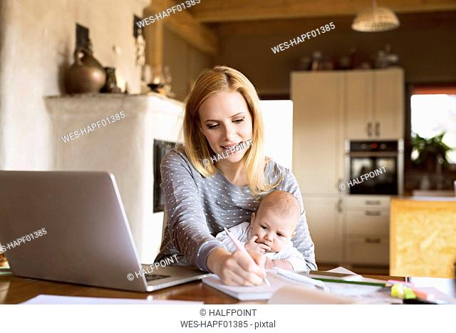 Mother with baby at home using laptop and taking notes