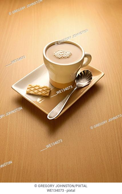 A cup of capuccino and a wafer on a plate in the morning